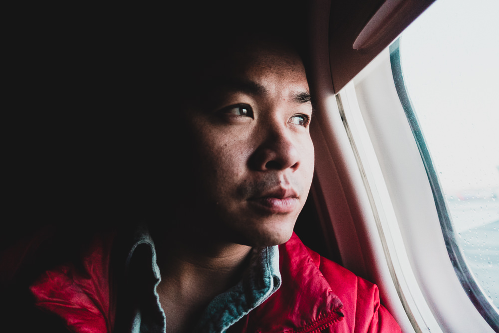 Man looking out of airplane window in first class