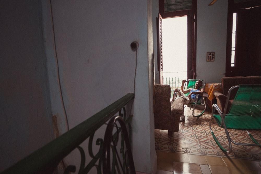 Portrait of old Cuban man on chair in Havana