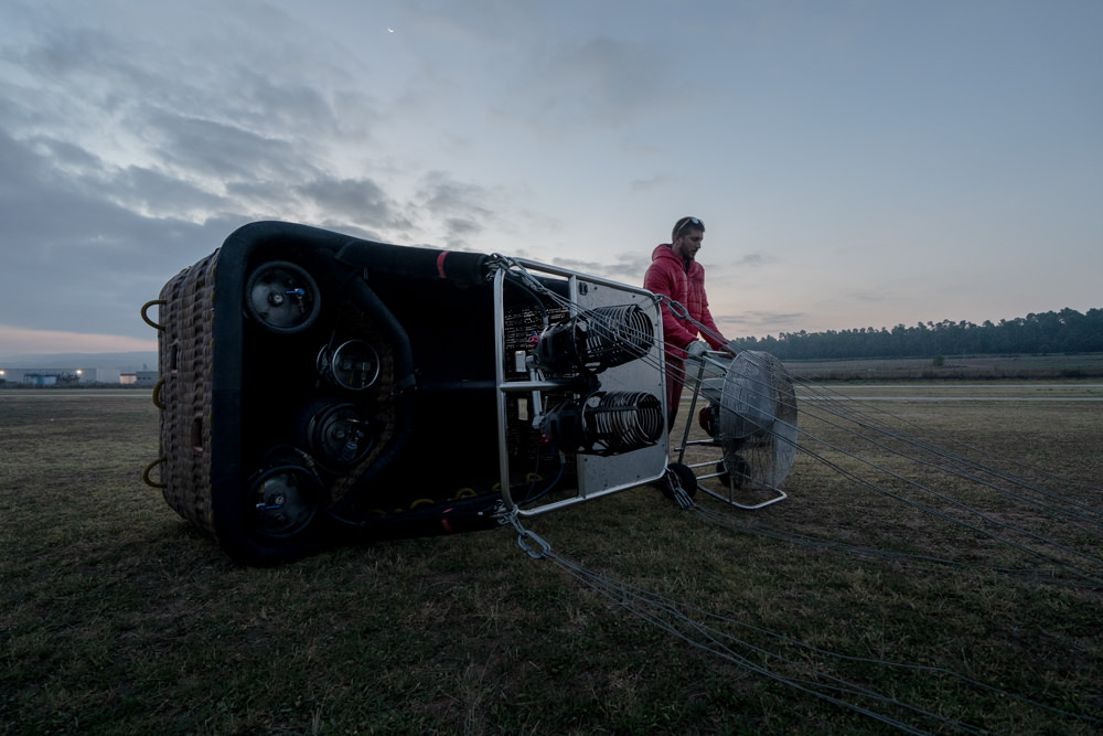 Pilot prepping hot air balloon at dawn